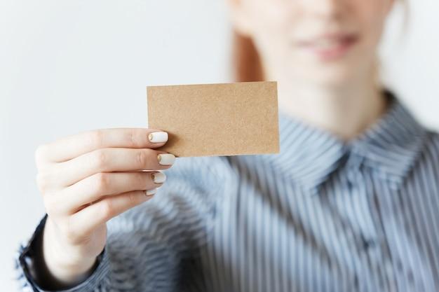 Close-up shot van vrouwelijke handen met een blanco visitekaartje Gratis Foto