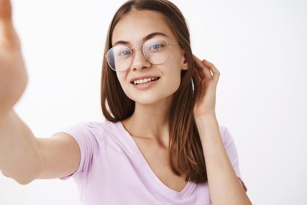 Close-up shot van zelfverzekerde knappe sensuele en vrouwelijke jonge vrouw haar achter het oor flirterige glimlachend vreugdevol bril nemen selfie genieten van blik van mooie schone huid Gratis Foto