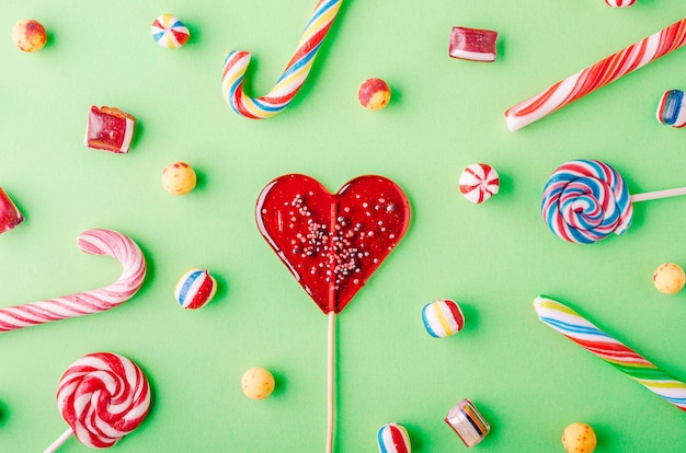 Close-up shot van zuurstokken en andere snoepjes op een groene achtergrond - perfcet voor een cool behang Gratis Foto
