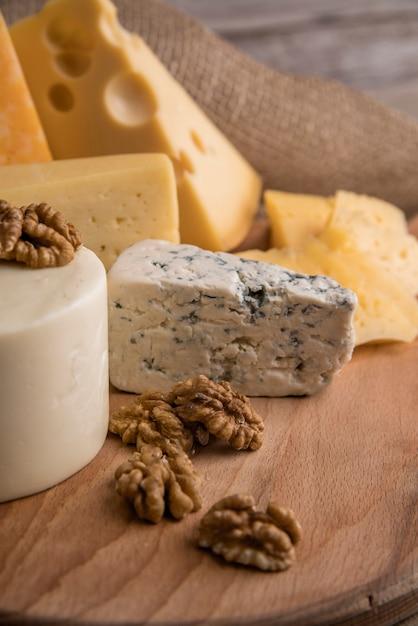 Close-up smakelijke verscheidenheid van kaas met walnoten Gratis Foto