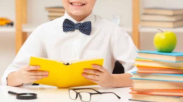 Close-up smiley jongen lezen Gratis Foto