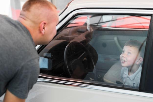 Close-up smiley jongen zit in de auto Premium Foto