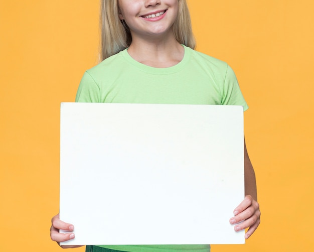Close-up smiley meisje met blanco vel papier Gratis Foto