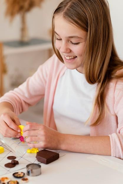 Close-up smiley meisje spelen met klei Gratis Foto