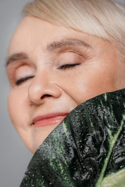 Close-up smiley vrouw met blad Gratis Foto