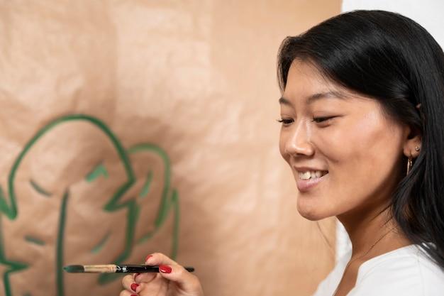 Close-up smiley vrouw met borstel Gratis Foto