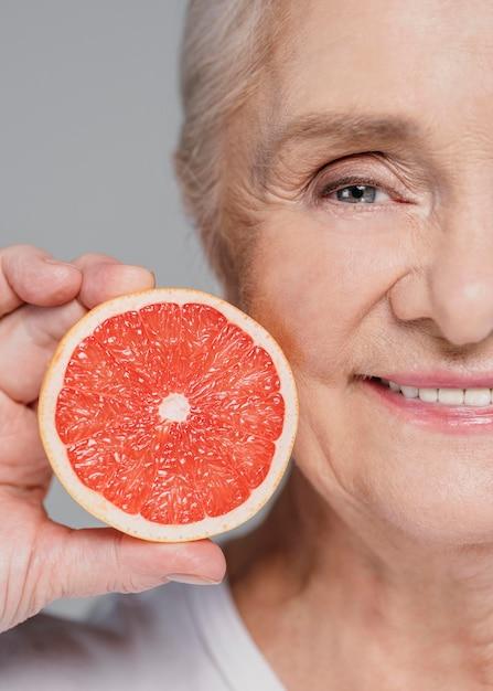 Close-up smiley vrouw met rode sinaasappel Gratis Foto