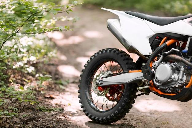 Close-up stijlvolle motorfiets geparkeerd in het bos Gratis Foto