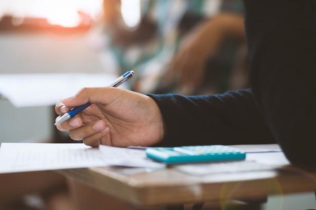 Close-up studenten schrijven en lezen examen antwoord bladen oefeningen in de klas van school met stress. Premium Foto