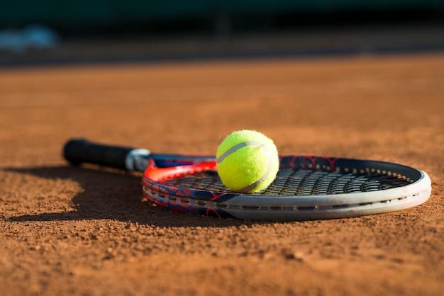 Close-up tennisbal op een racket dat op de vloer wordt geplaatst Gratis Foto