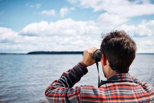 Close-up terug portret van man kijkt door een verrekijker Gratis Foto