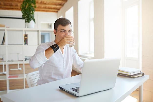 Close-up van aantrekkelijke jonge zakenman draagt een wit overhemd op kantoor Gratis Foto
