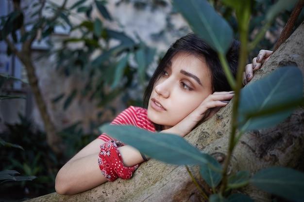Close-up van aantrekkelijke romantische jonge dame met bob kapsel haar hoofd rustend op boomstam en zijwaarts kijken met dromerige doordachte gezichtsuitdrukking. selectieve aandacht voor het gezicht van het meisje Gratis Foto
