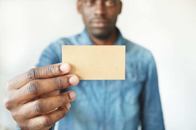 Close-up van afrikaanse man handen met visitekaartje Gratis Foto