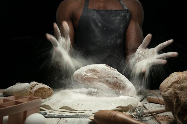 Close up van afro-amerikaanse man kookt vers ontbijtgranen, brood, zemelen op houten tafel. lekker eten, voeding, ambachtelijk product. glutenvrij eten, gezonde levensstijl, biologisch en veilig geproduceerd. handgemaakt. Gratis Foto