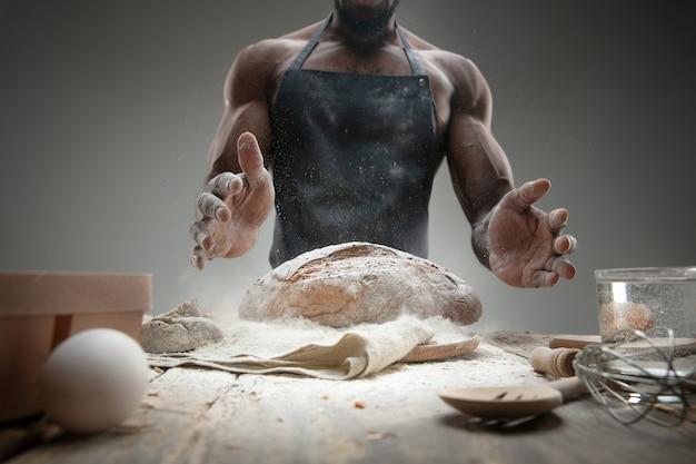 Close up van afro-amerikaanse man kookt vers ontbijtgranen, brood, zemelen op houten tafel. lekker eten, voeding, ambachtelijk product Gratis Foto
