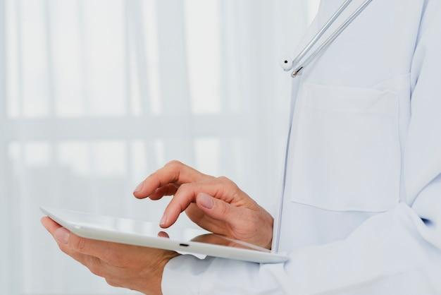 Close-up van arts die tablet gebruikt Gratis Foto