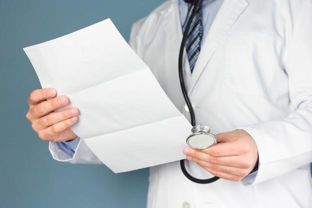 Close-up van arts met een stethoscoop medische verslag in de hand te houden Gratis Foto