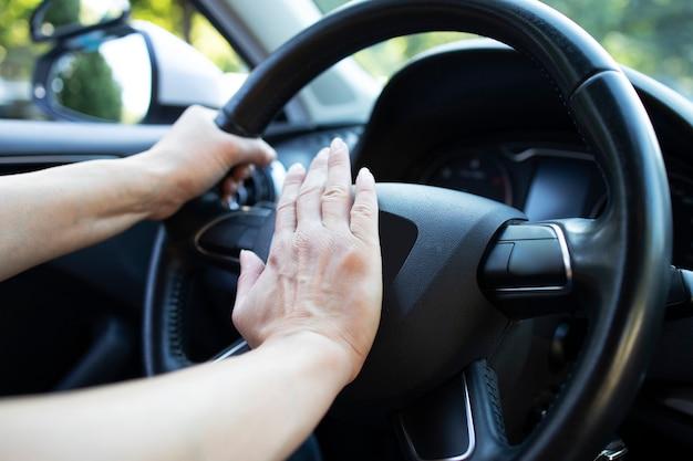 Close-up van auto stuurwiel en hand op hoorn of toeteren te drukken. Premium Foto