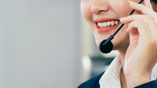 Close-up van aziatische jonge mooie vrouw personeel bij servicedesk praten over handsfree telefoon in een callcenter Premium Foto