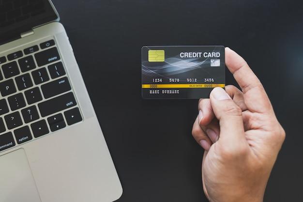 Close up van aziatische mannen met een creditcard en online winkelen via laptop Premium Foto