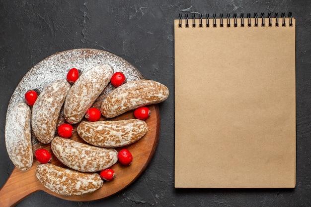 Close-up van banaan koekjes met fruit op bruin snijplank en notebook op donker Gratis Foto