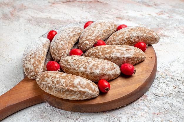 Close-up van banaan koekjes met fruit op bruin snijplank op wit Gratis Foto