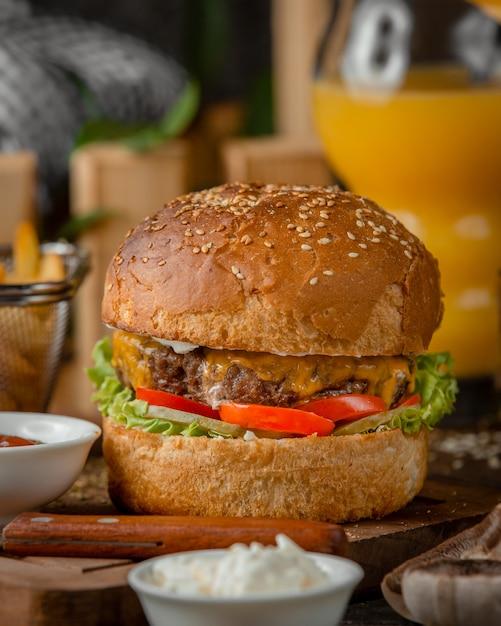 Close up van beef burger met gesmolten cheddar, tomaat, sla en mayo Gratis Foto