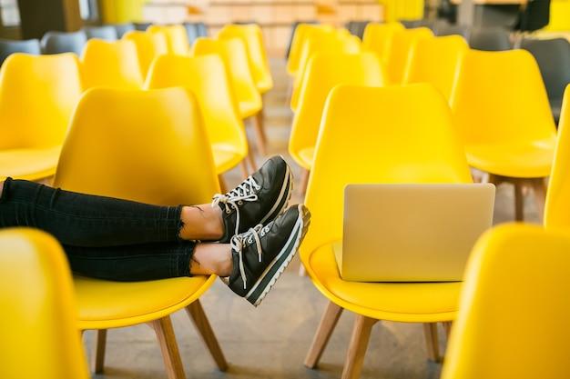 Close-up van benen van stijlvolle jongedame zitten in collegezaal met laptop, klas met veel gele stoelen, schoenen sneakers, schoenen modetrend Gratis Foto