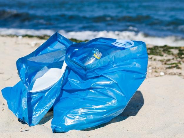 Close-up van blauwe vuilniszak op zand bij strand Gratis Foto