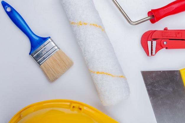 Close-up van bouwhulpmiddelen als verfborstel en rol de pijpsleutel van de veiligheidshelm en stopverfmes op witte achtergrond Gratis Foto