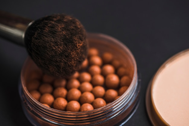 Close-up van bronzing parels en make-up borstel Gratis Foto
