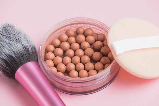 Close-up van bronzing parels; spons en make-upborstel op roze achtergrond Gratis Foto