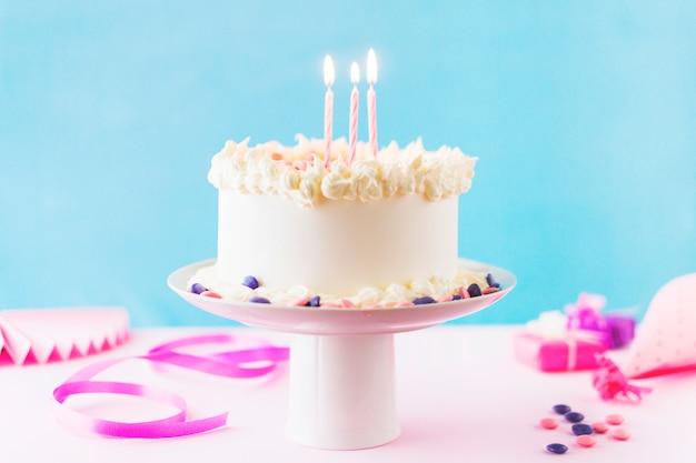 Close-up van cake met brandende kaarsen op roze achtergrond Gratis Foto