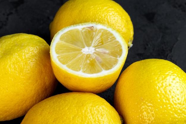 Close-up van citroenen en een half op zwart Gratis Foto