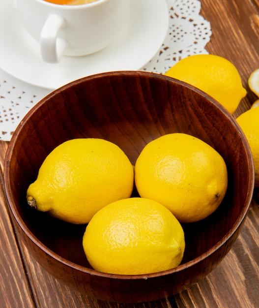 Close-up van citroenen in houten kom met kopje thee op houten achtergrond Gratis Foto