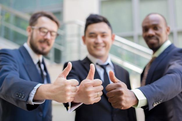 Close-up van commercieel team dat hun duimen tegenhoudt Gratis Foto