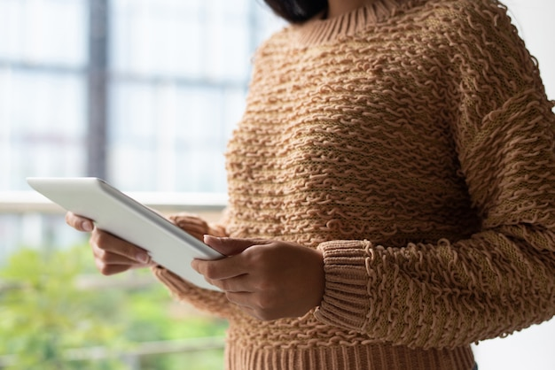 Close-up van dame in gebreide sweater het letten op video op tablet Gratis Foto