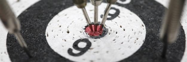 Close-up van dartbord. darts raken bij het bereiken van het centrale doel. Premium Foto
