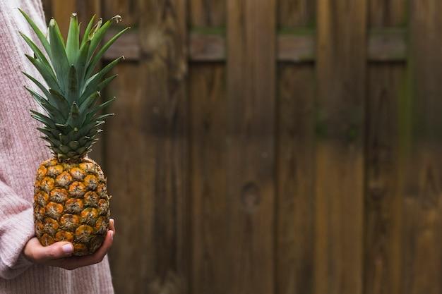 Close-up van de ananas van de de handholding van een persoon tegen houten muur Gratis Foto