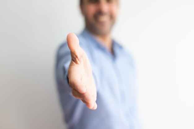Close-up van de bedrijfsmens die hand voor handdruk aanbiedt Gratis Foto