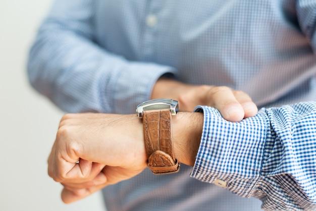Close-up van de bedrijfsmens die tijd controleert op horloge Gratis Foto