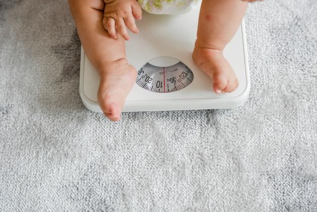 Close-up van de benen van een baby op een weegschaal Gratis Foto