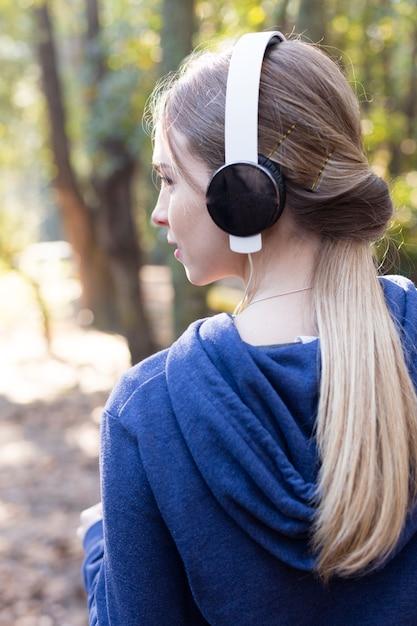 Close-up van de blonde meisje luisteren naar muziek in openlucht Gratis Foto