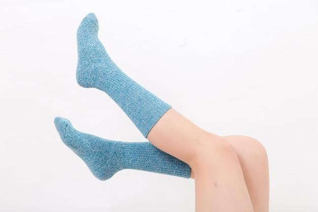 Close-up van de blote benen van een jonge vrouw die blauwe sokken met zijn voeten draagt. geïsoleerd op witte achtergrond studio verlichting Premium Foto