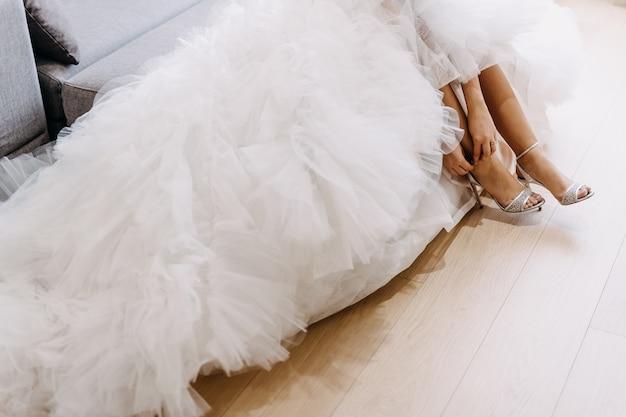 Close-up van de bruid trouwjurk dragen, haar schoenen aantrekken. Premium Foto