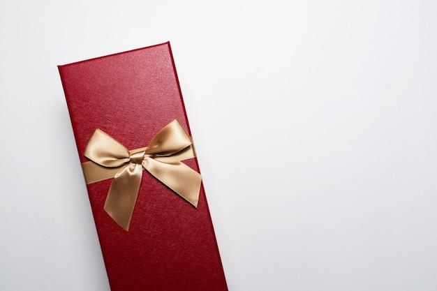 Close-up van de doos van de kerstmisgift van rode kleur met gouden boog, die op witte achtergrond met exemplaarruimte wordt geïsoleerd. Premium Foto