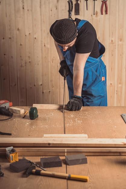 Close-up van de een man-bouwer zag een bord Premium Foto