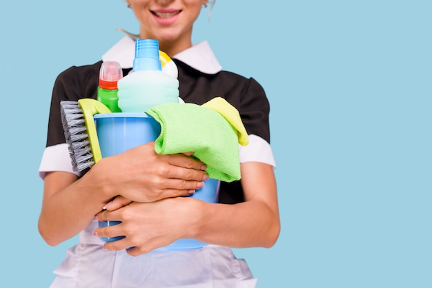 Close-up van de glimlachende emmer van de huishoudsterholding met het schoonmaken van apparatuur tegen blauwe achtergrond Gratis Foto