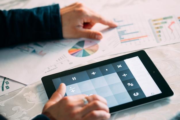 Close-up van de hand die van businessperson bill on digital tablet over bureau analyseren. Premium Foto